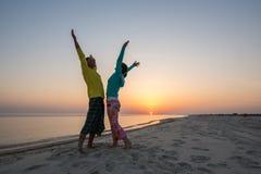 Coppie allegre dei viaggiatori divertendosi sulla spiaggia Immagine Stock Libera da Diritti