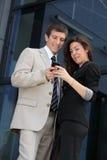 Coppie allegre di affari che esaminano un telefono astuto Fotografia Stock