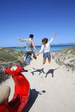Coppie allegre di salto che si dirigono alla spiaggia Fotografia Stock