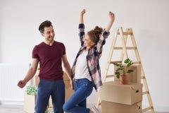 Coppie allegre divertendosi in loro nuovo appartamento fotografia stock libera da diritti