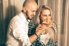 Coppie allegre nell'amore divertendosi con la pizza al partito Fotografia Stock Libera da Diritti