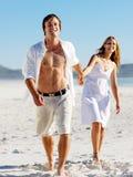 Coppie ambulanti spensierate della spiaggia Fotografie Stock Libere da Diritti