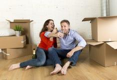 Coppie americane felici che si siedono sul pavimento che disimballa insieme celebrazione con il pane tostato del champagne che si Fotografia Stock Libera da Diritti