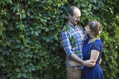 Coppie amorose che abbracciano su un fondo dei cespugli verdi honeymoon Fotografie Stock Libere da Diritti