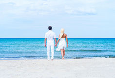 Coppie amorose che camminano e che abbracciano su una spiaggia di estate fotografia stock libera da diritti