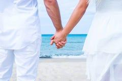 Coppie amorose che camminano e che abbracciano sulla spiaggia fotografie stock