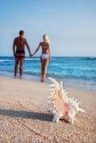 Coppie amorose che camminano sulla spiaggia della sabbia di mare fotografia stock