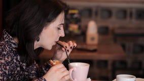 Coppie amorose che parlano in un caffè che mangia un croissant e un panino e bevande beventi del caffè archivi video