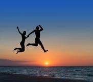 Coppie amorose che saltano altamente nel cielo alla stazione balneare Fotografia Stock