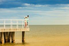Coppie amorose dei pantaloni a vita bassa sul pilastro del mare Immagini Stock Libere da Diritti