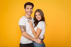 Coppie amorose felici che abbracciano contro il fondo giallo immagini stock libere da diritti