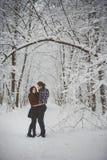 Coppie amorose felici che camminano nella foresta nevosa di inverno fotografia stock libera da diritti