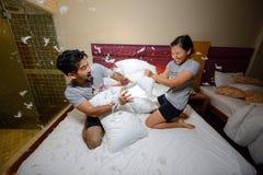 Coppie amorose felici che hanno una lotta di cuscino a letto alla notte Fotografia Stock