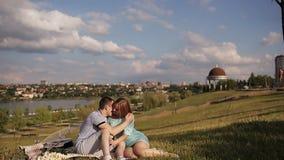 Coppie amorose felici che riposano nel parco sul prato inglese verde stock footage