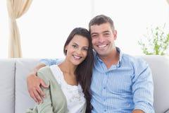 Coppie amorose felici che si siedono sul sofà Immagini Stock Libere da Diritti