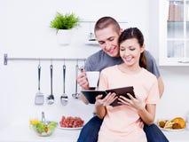 Coppie amorose felici nella cucina immagini stock