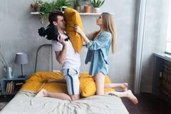 Coppie amorose nella camera da letto che ha lotta di cuscino immagini stock libere da diritti