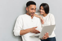 Coppie amorose sorridenti che chiacchierano dal computer portatile Fotografia Stock