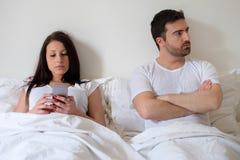 Coppie annoiate ed uomo preoccupato dalla sua dipendenza da Internet della moglie immagini stock