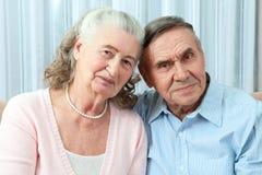 Coppie anziane affettuose con i bei sorrisi amichevoli d'orientamento che posano insieme in un abbraccio vicino nel loro salone P fotografia stock libera da diritti