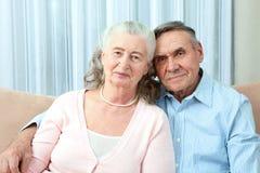 Coppie anziane affettuose con i bei sorrisi amichevoli d'orientamento che posano insieme in un abbraccio vicino nel loro salone P fotografia stock