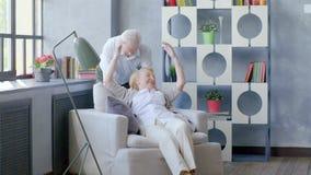Coppie anziane amorose e felici in un appartamento moderno Il marito bacia la sua moglie archivi video
