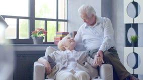 Coppie anziane amorose e felici in un appartamento moderno parlano e sorridono video d archivio