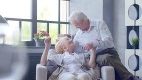 Coppie anziane amorose e felici in un appartamento moderno parlano, naso di tocchi del marito della sua moglie stock footage