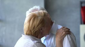 Coppie anziane amorose e felici in un appartamento moderno parlano, sorridono, si abbracciano e si baciano stock footage