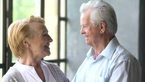 Coppie anziane amorose e felici in un appartamento moderno parlano, sorriso ed esaminare la macchina fotografica stock footage
