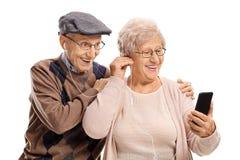 Coppie anziane che ascoltano insieme la musica su un telefono Fotografia Stock