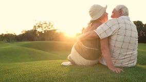 Coppie anziane che baciano sull'erba verde video d archivio