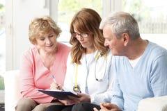 Coppie anziane che consultano medico femminile Fotografia Stock Libera da Diritti