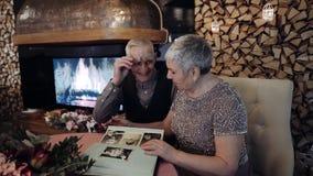 Coppie anziane che guardano album di foto stock footage