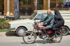 Coppie anziane che guidano un motociclo tramite le vie della città, Kashan, Fotografie Stock