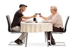 Coppie anziane che producono un pane tostato con vino Immagine Stock Libera da Diritti