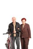 Coppie anziane che si tengono per mano e che spingono una bici Fotografia Stock