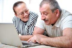 Coppie anziane con il computer portatile fotografia stock
