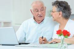 Coppie anziane con il computer portatile e la mappa Fotografia Stock