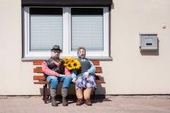 Coppie anziane fatte di paglia che si siede su un banco di legno davanti ad una casa immagini stock libere da diritti