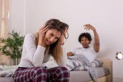 Coppie arrabbiate che discutono nella camera da letto immagini stock