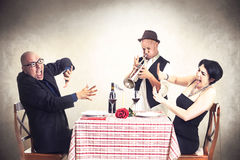 Coppie arrabbiate di disturbo da un musicista della tromba mentre cenando Immagini Stock Libere da Diritti