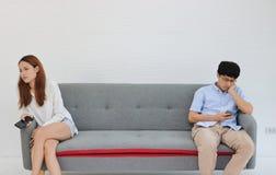 Coppie asiatiche arrabbiate infelici che si siedono via dopo la discussione in salone Cattivo concetto delle coppie di relazione immagine stock libera da diritti