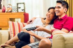 Coppie asiatiche che guardano TV Fotografia Stock Libera da Diritti