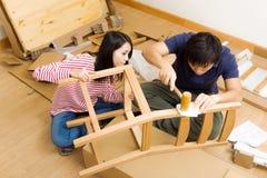 Coppie asiatiche che montano nuova sedia Fotografia Stock Libera da Diritti