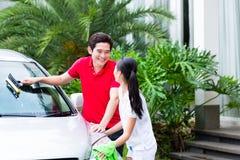 Coppie asiatiche che puliscono insieme automobile Fotografia Stock