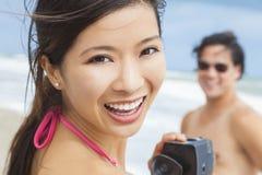Coppie asiatiche della donna alla spiaggia che prende video o fotografia Fotografie Stock