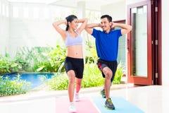 Coppie asiatiche di forma fisica all'allenamento di sport nella casa tropicale Immagine Stock