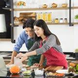 Coppie asiatiche in grembiule produrre insieme un'insalata fotografie stock