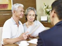 Coppie asiatiche senior che incontrano un rappresentante di vendite fotografia stock